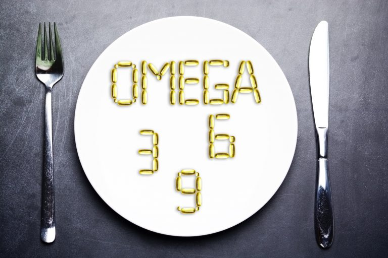 nutritional supplement of omega 3, omega 6 or omega 9 from yellow fish oil capsules on plate