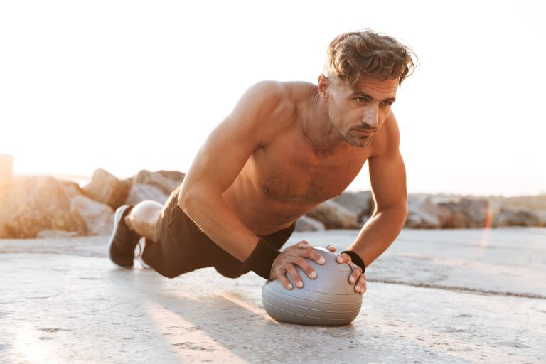 Portrait of a focused shirtless sportsman doing exercises with small fitness ball outdoors